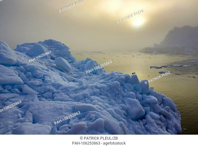 25.06.2018, Gronland, Denmark: In the late evening in the dense fog to the late afternoon sun icebergs drift in the sea in front of the coastal town of...
