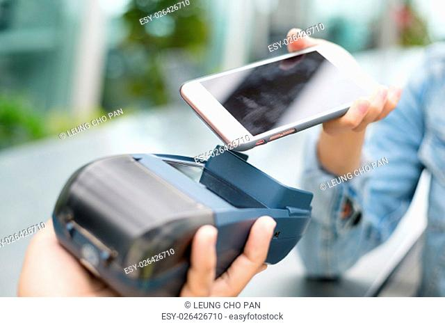 Customer using cellphone to pay with NFC technology