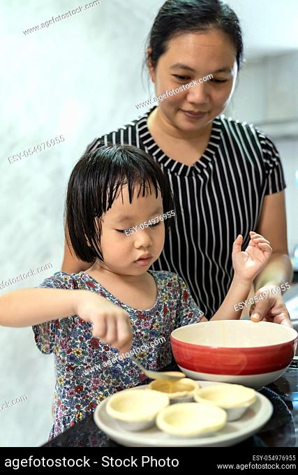 Asian girl cooking egg tart bakery with her mom, housework for child make executive function for kid. Houseworking food lifstyle and family concept