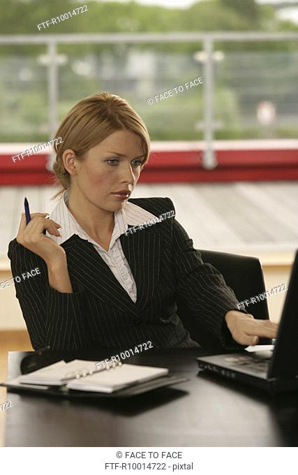 A blonde businesswoman with a laptop and a diary beside her