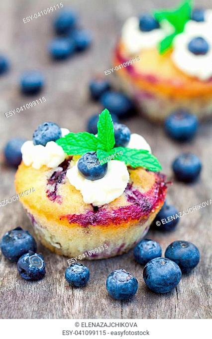 fresh muffins with blueberry and mint on wooden background