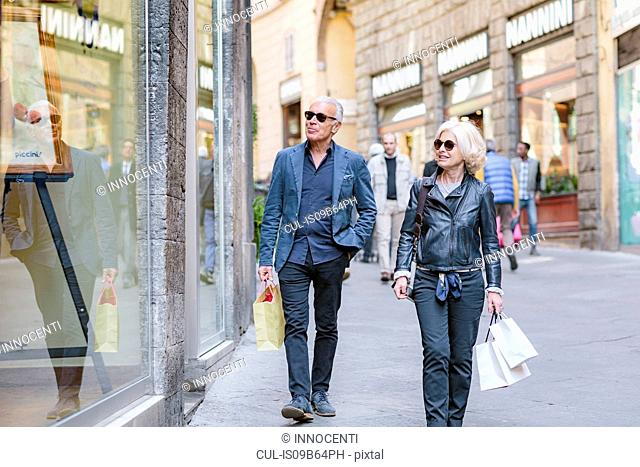 Tourist couple strolling with shopping bags on city street, Siena, Tuscany, Italy
