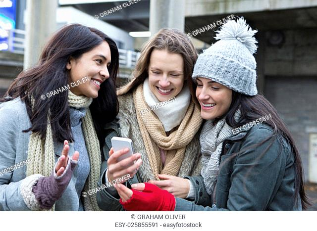 Three young women in the city, looking at something on a smartphone