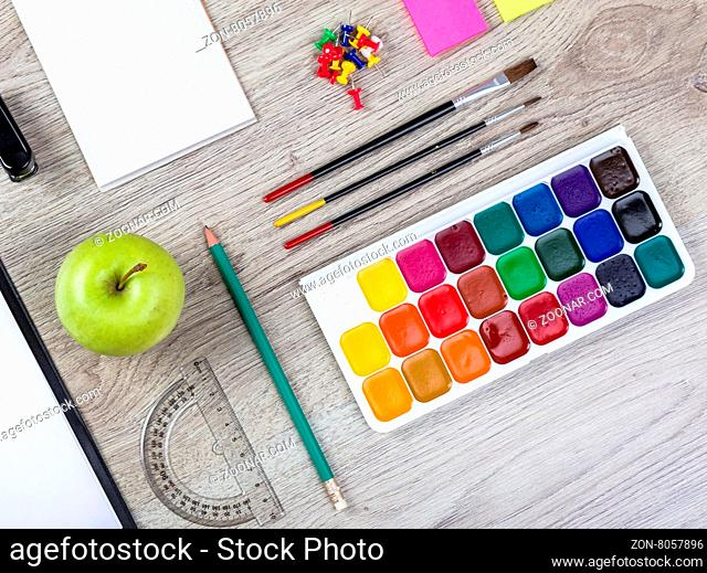 Back to school note book, pencils, loupe, green apple on wooden table