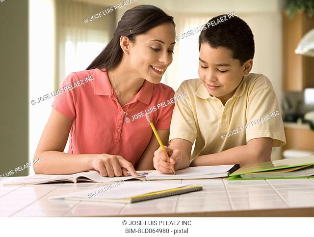 Hispanic mother helping son do homework