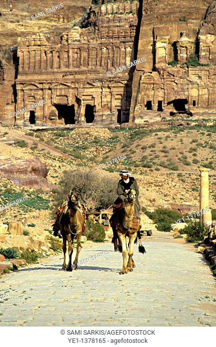 Man riding a camel down a cobblestone road near the entrance to the Royal Tombs carved into the cliffs at Petra, Jordan