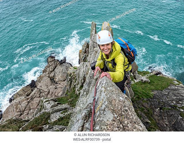 UK, Cornwall, smiling woman climbing on Commando Ridge