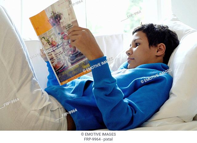 Young woman reading magazine on couch