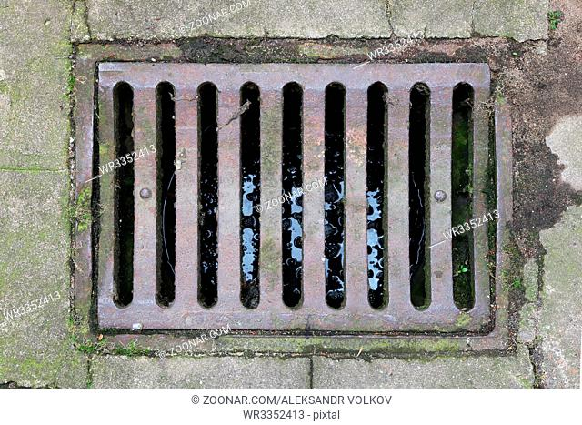 Old rusty iron grille of the rain sewer system of the city. Top view shot