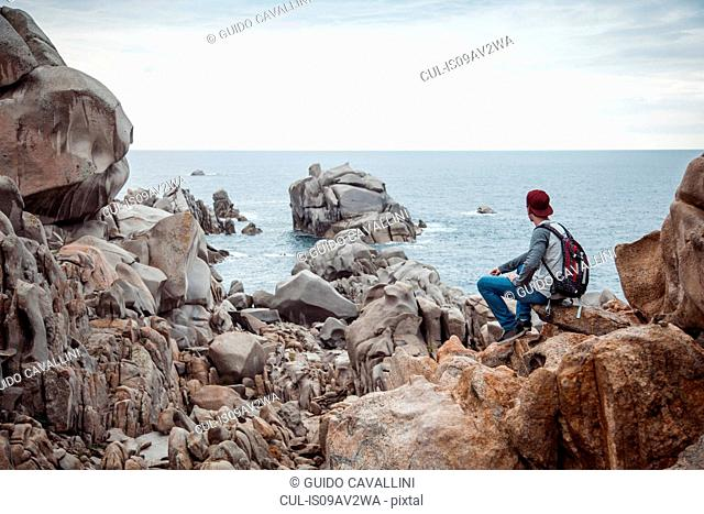 Rear view of young man sitting on rocks looking at view of ocean, Costa Smeralda, Sardinia, Italy
