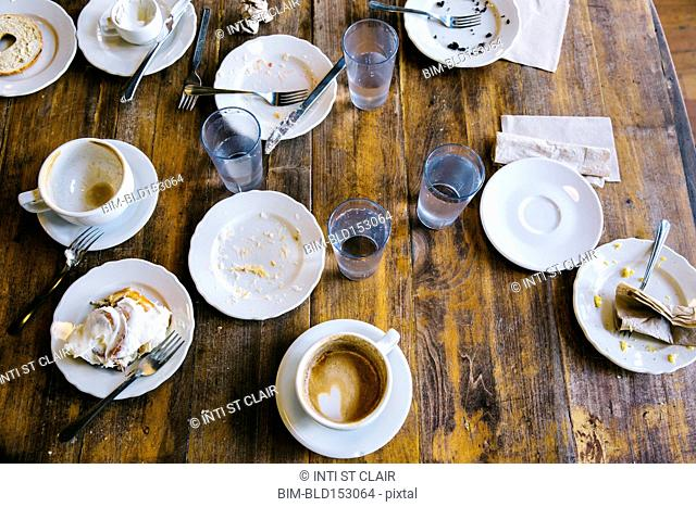 Empty plates, coffee cups and glasses on cafe table