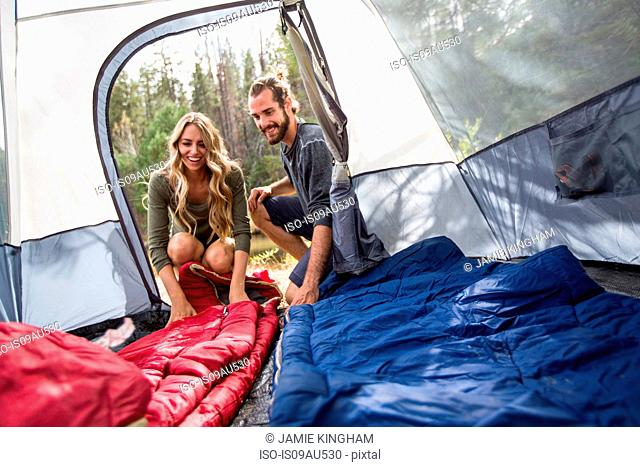 Happy young couple looking into tent, Lake Tahoe, Nevada, USA