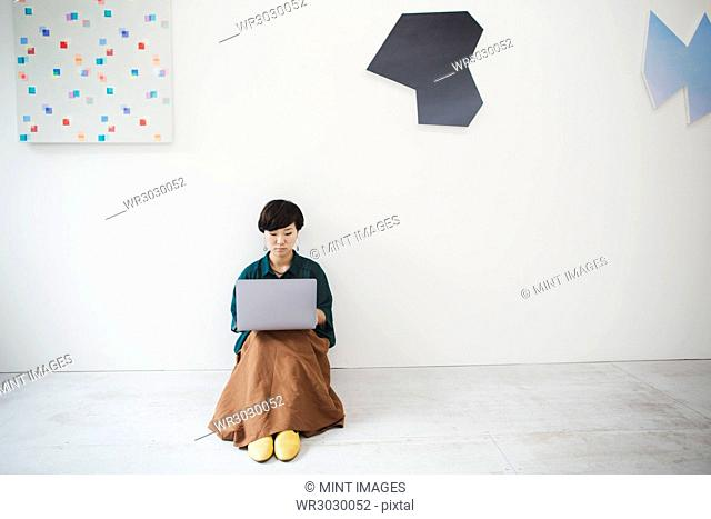 Woman with short black hair wearing green shirt sitting on floor in art gallery, balancing laptop on her knees