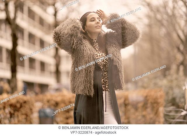 fashionable woman in city, hands on head, fixing hairs, in Munich, Germany