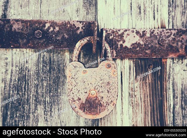 metallic old rusty padlock on old wooden door, background, retro style