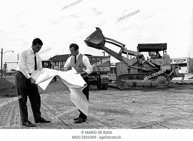 Italian brothers Lorenzo Galli and Michele Galli, owners of a company in Melbourne skilled in street building, watching a plan in the middle of a building site