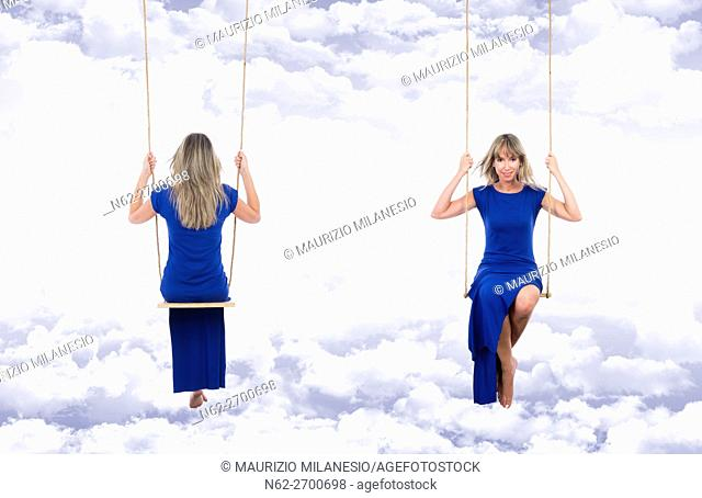 Smiling and relaxed blonde woman, front and back view, wearing a long blue dress on the swing, suspended through the clouds of a fantasy blue sky