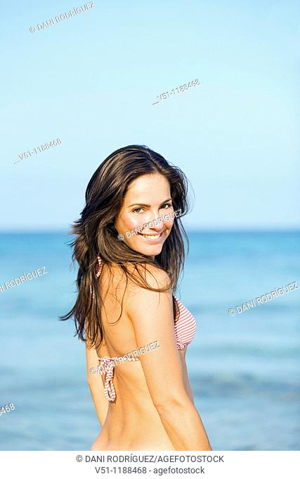 Portrait of a brunette woman smiling at camera at the beach in Ibiza, Balearic Islands