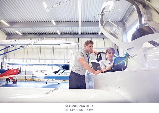 Mechanic engineers working in airplane cockpit in hangar