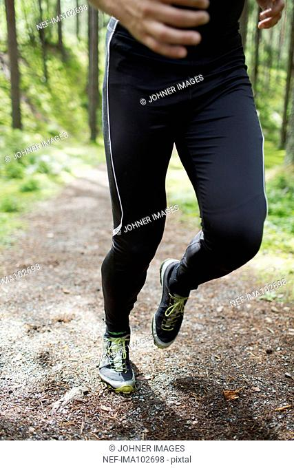 Mid adult man running through forest, low section