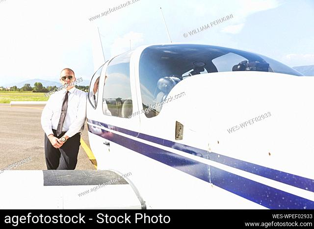 Pilot standing by his sports plane