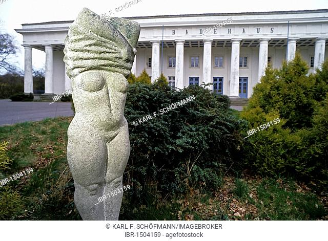 Woman pulling her dress over her head, stone sculpture in front of the historic bathhouse, Lauterbach near Putbus, Ruegen island, Baltic Sea