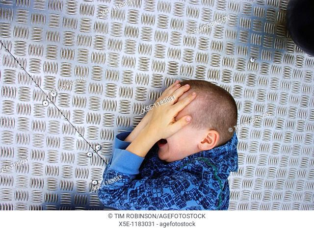 Head and shoulders 9 year boy lying on floor covering face with hands
