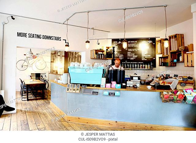 Independent coffee shop, business owner working behind counter