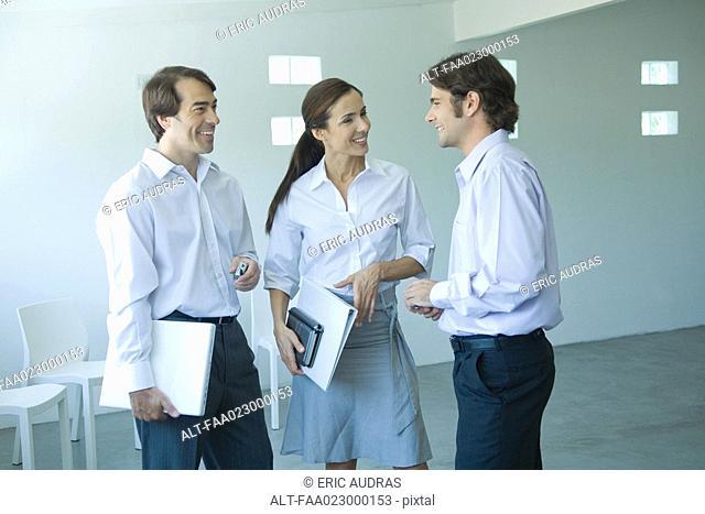 Three business associates chatting and smiling, three quarter length