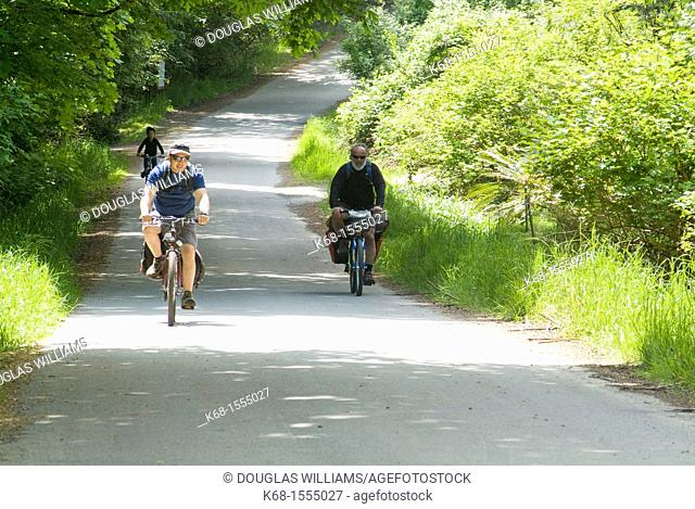 three people bicycling on a country road on Saltspring Island, BC, Canada