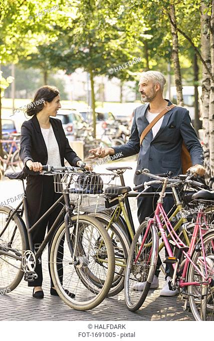 Business colleagues talking while standing with bicycles in parking lot