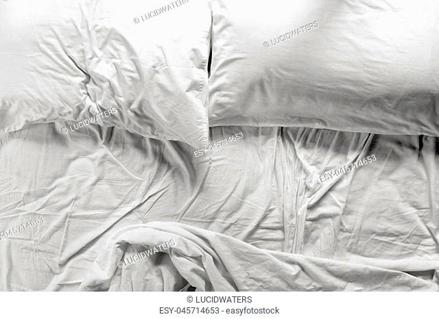 Flat lay view of an unmade bed in a bedroom with two pillows and crumpled bed sheet, after waking up in the morning. Couple lifestyle concept