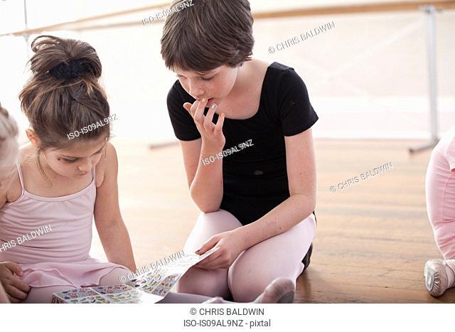 Girls swapping stickers in ballet school
