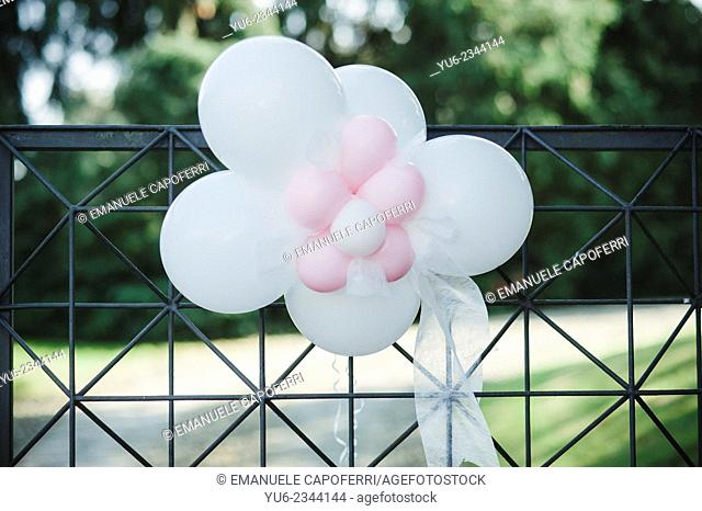 Pink and white balloons hanging from the gate of the house
