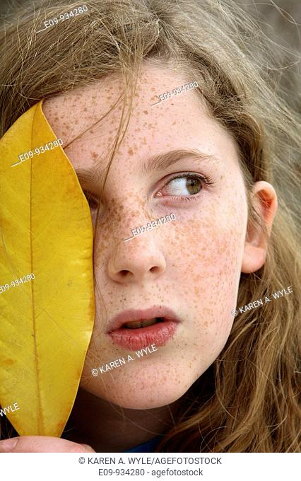 13-year-old girl with gold-brown messy hair and freckles, holding large yellow leaf over the right side of her face, a wary expression