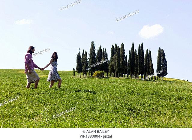 Italy, Tuscany, Val D'Orcia, Couple walking in meadow