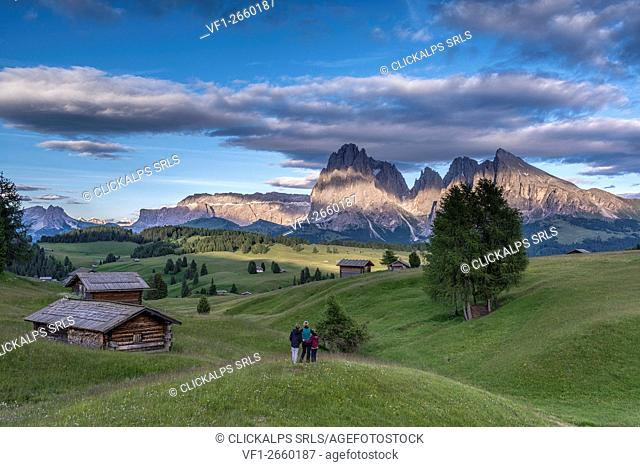 Alpe di Siusi/Seiser Alm, Dolomites, South Tyrol, Italy. Mountaineers on the Alpe di Siusi admire the alpenglow. In the background the Sella