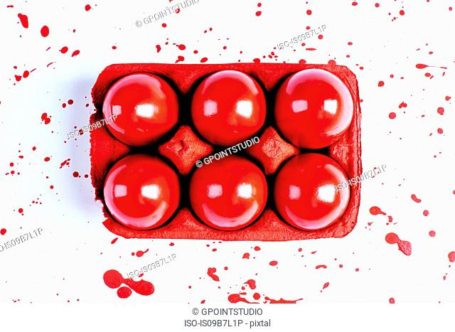 Overhead view of red painted easter eggs in carton with splatters on white background