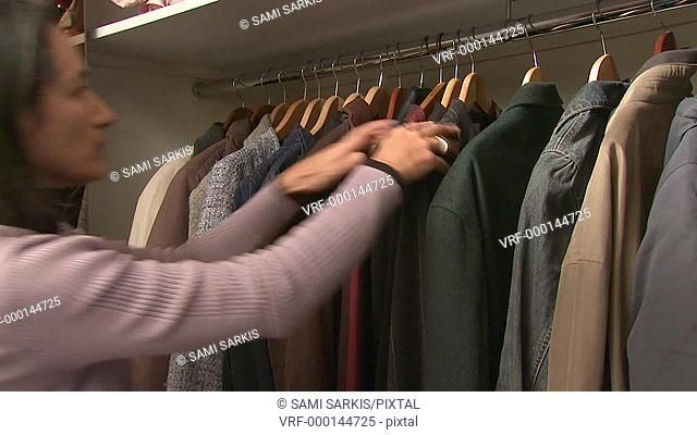 Woman choosing her coat from closet