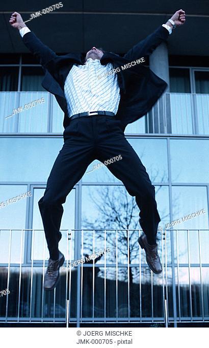 A salesman, businessman, tradesman, employee, officer, young man jumping for joy, jubilating