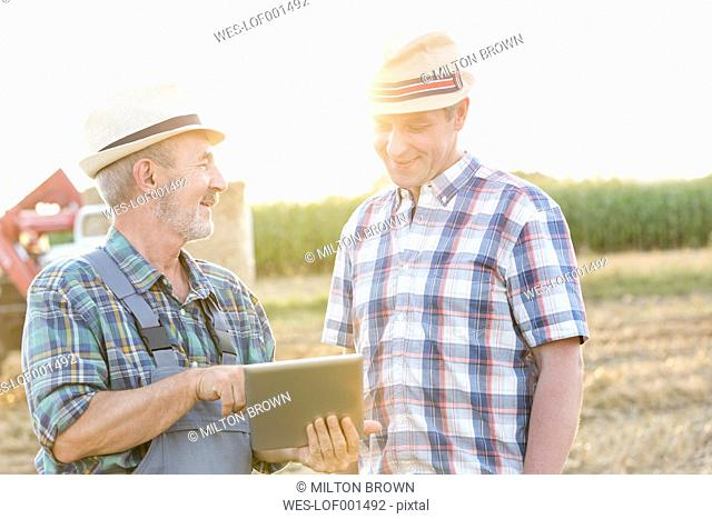Two farmers with digital tablet discussing on field