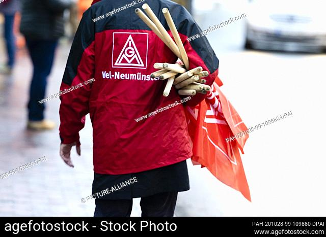 28 October 2020, Schleswig-Holstein, Kiel: A participant of a demonstration carries flags of the IG Metall under his arm