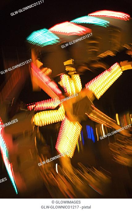 Lights glowing on a carnival ride at night, California, USA