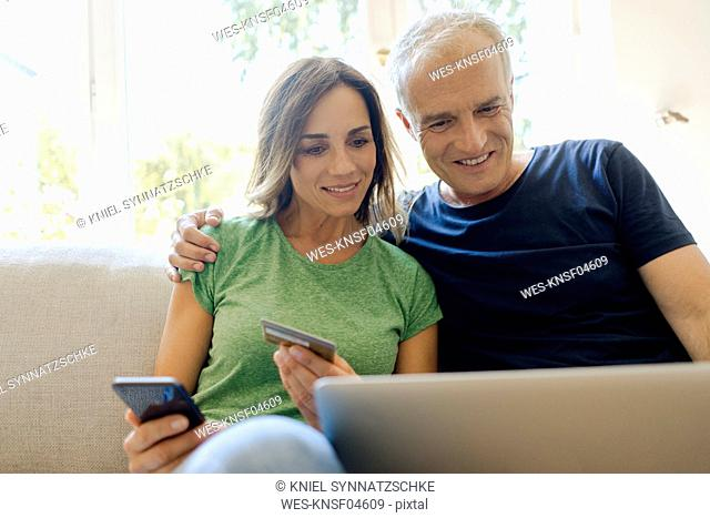 Smiling mature couple sitting on couch at home shopping online with laptopand smartphone