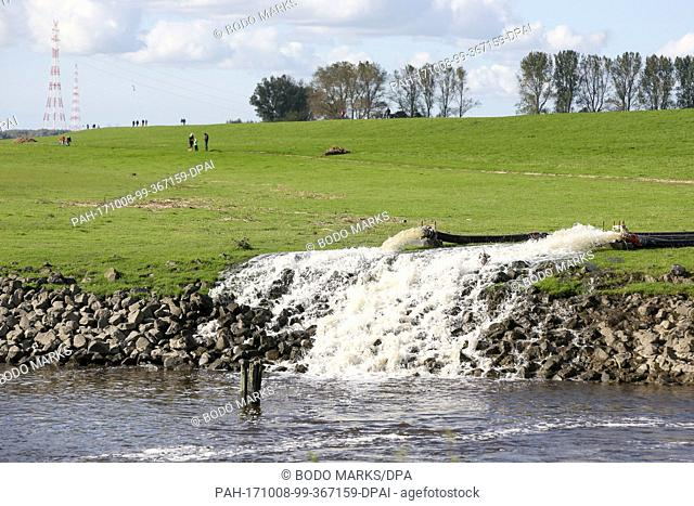 Water is pumped over a dike, into the river Elbe by fire department forces and the technical assistance department in Wedel, Germany, 8 October 2017