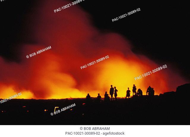 Hawaii, Big Island, Hawaii Volcanoes National Park, tourists watch lava flow into ocean, nighttime glow