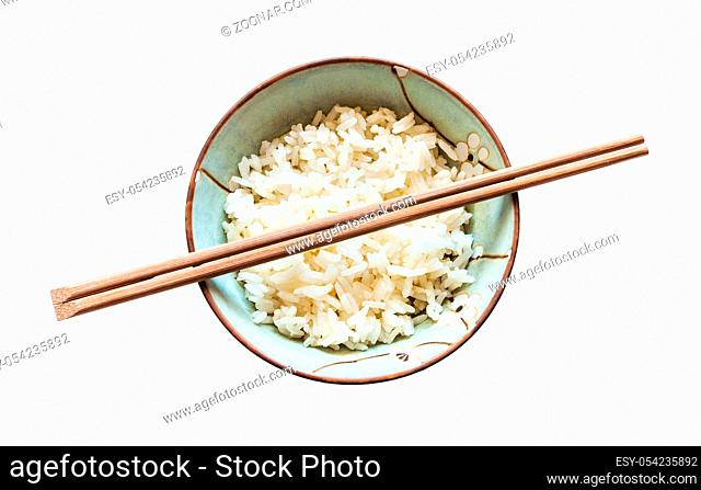 top view of chopsticks above cup with boiled rice isolated on white background
