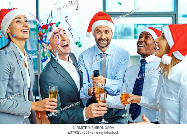Happy colleagues in Santa caps with champagne having Christmas fun in office