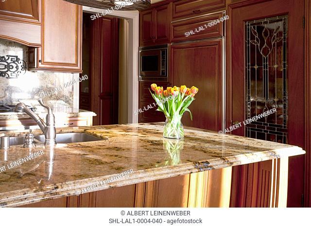 Vase of tulips on kitchen countertop