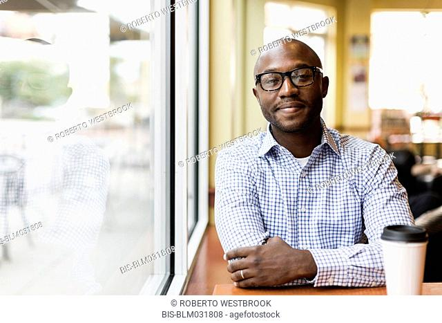 Black man having cup of coffee in cafe